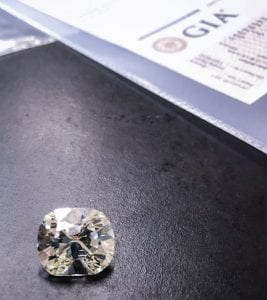 Large cushion cut diamond next to a GIA diamond grading report